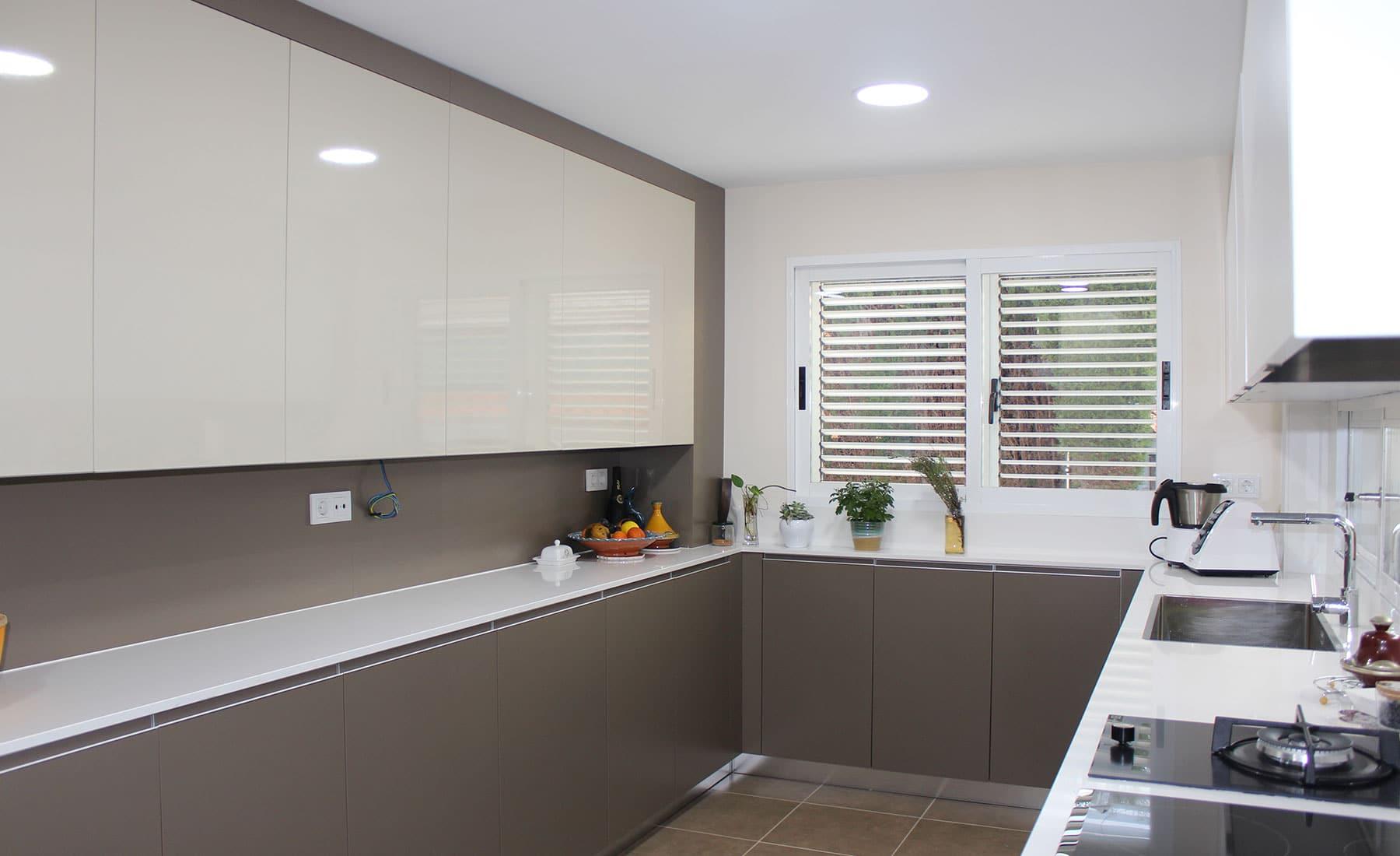 Vista de cocina con forma de U y colores gris y blanco