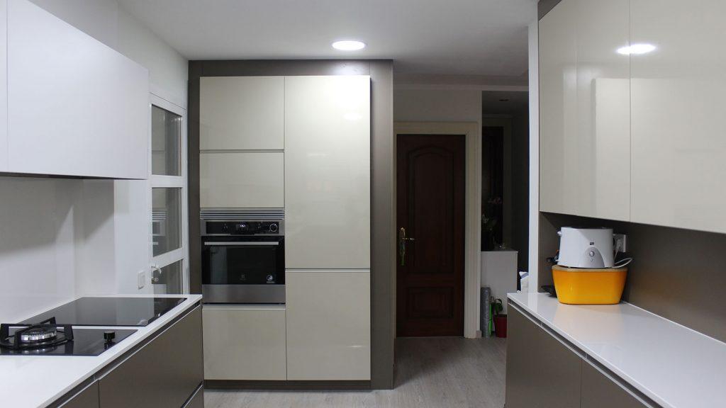 Dos frentes paralelos con muebles columna con frigorífico y horno integrado al fondo