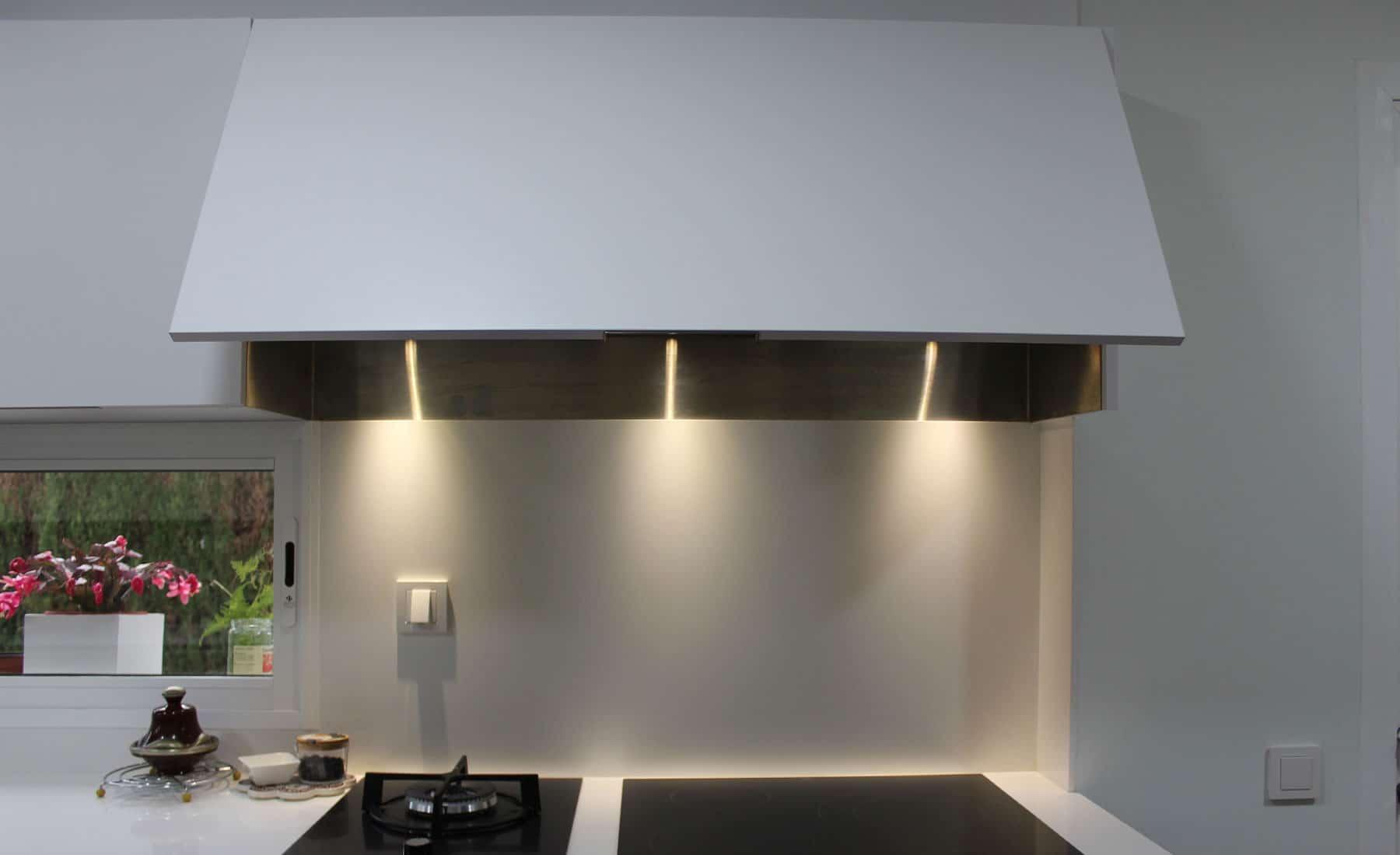 Detalle de campana de cocina integrada en mueble alto abatible.