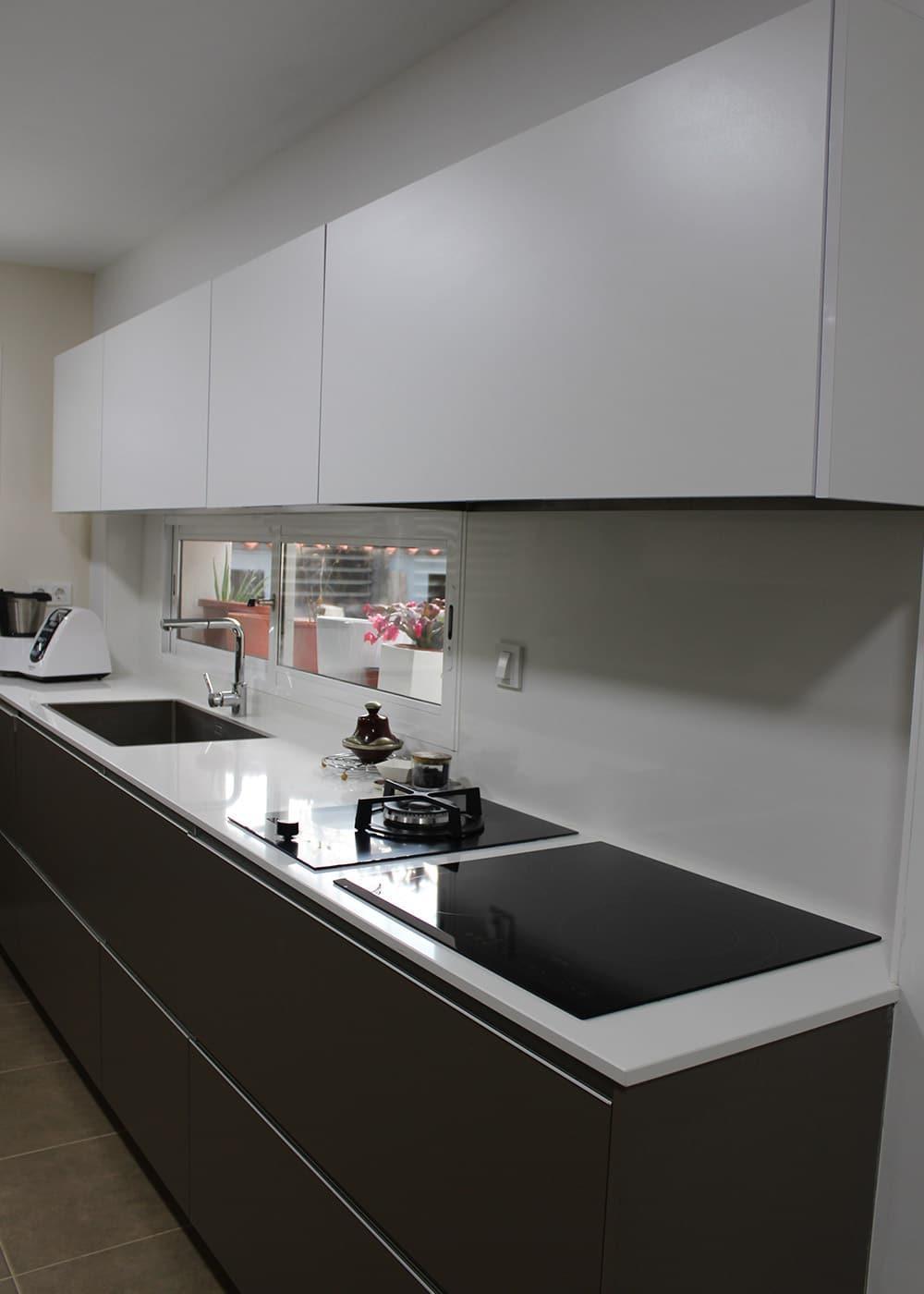 Detalle de muebles bajos y altos de cocina en color gris y blanco mate