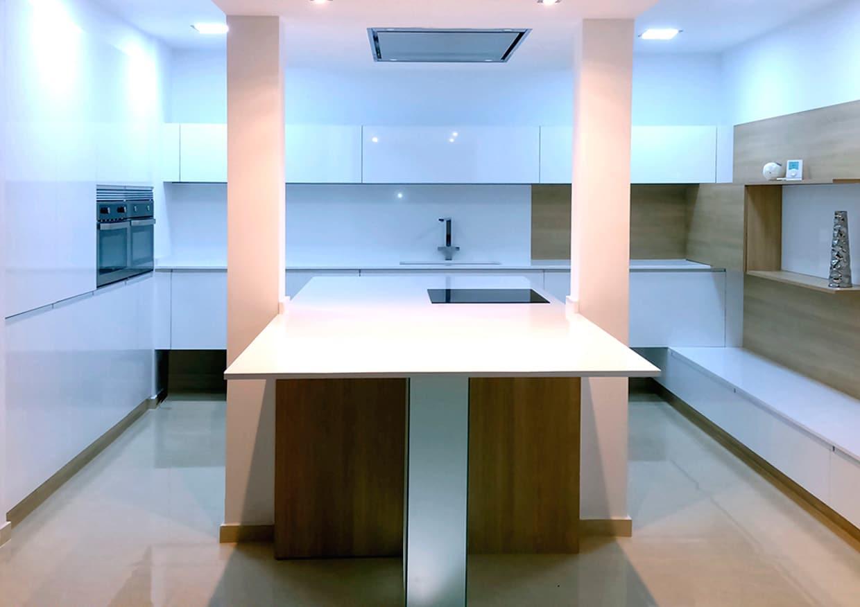 cocina moderna blanca con isla y campaña integrada en techo