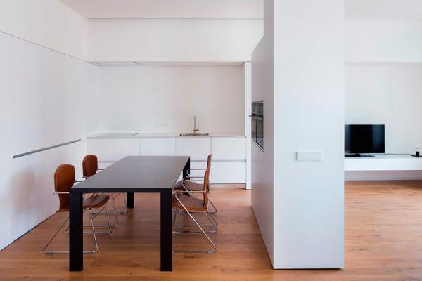 Cocina moderna en blanco abierta al salón en colaboración con Dot Partners