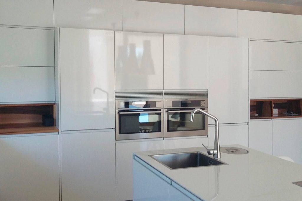Frende de columnas en blanco brillo con electrodomésticos integrados