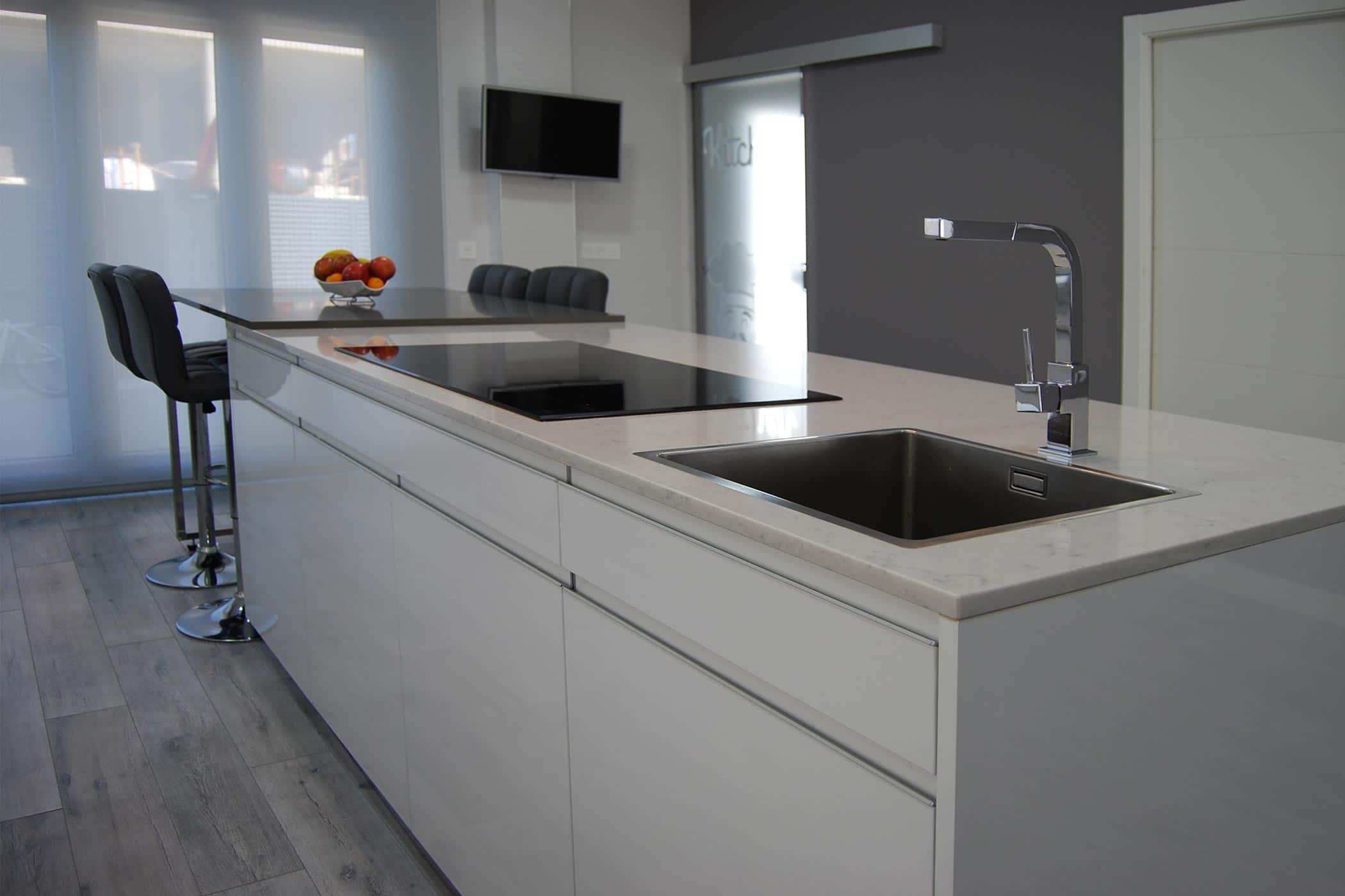 Detalle de isla de cocina en blanco y encimera en marmol