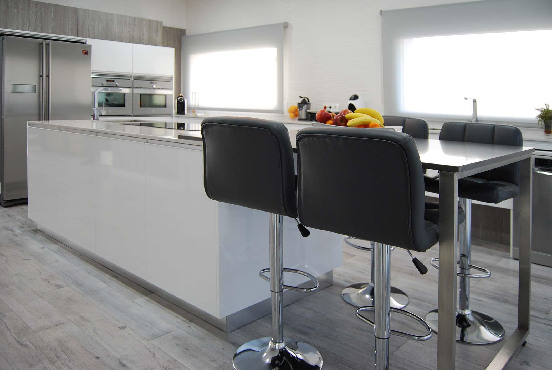 Cocina blanca en isla con mesa elevada