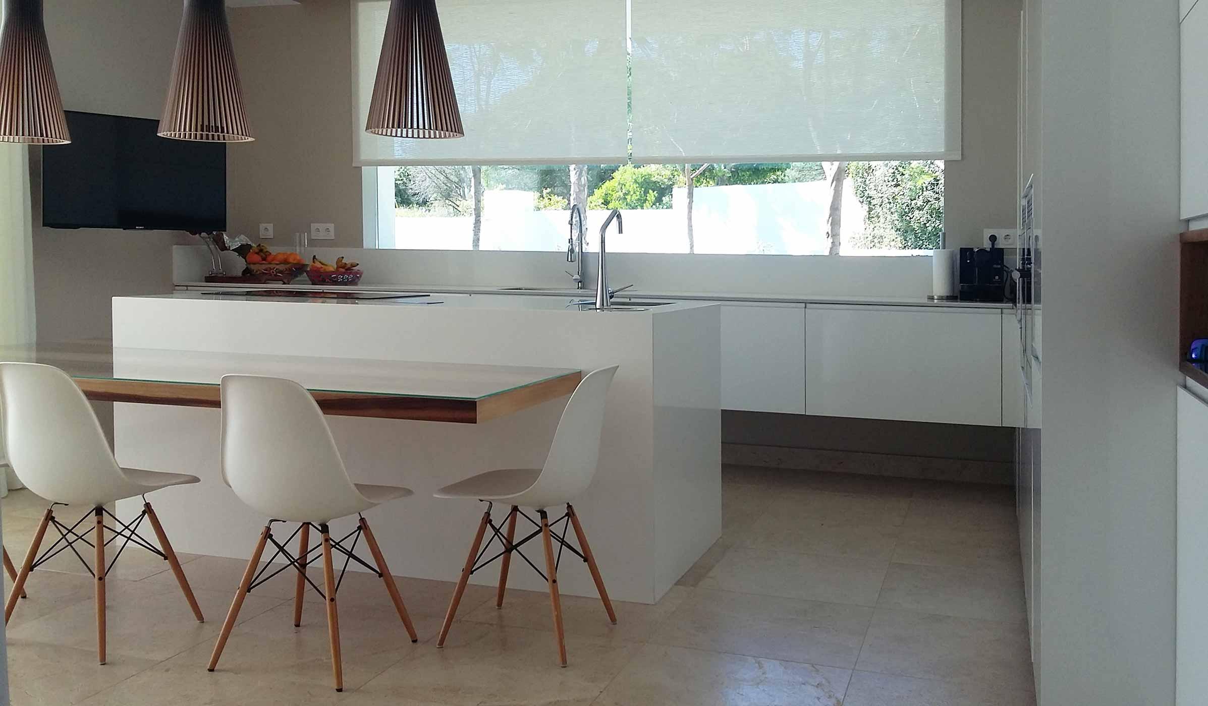 Vista general de cocina en color blanco brillo en forma de ele, con isla y mesado
