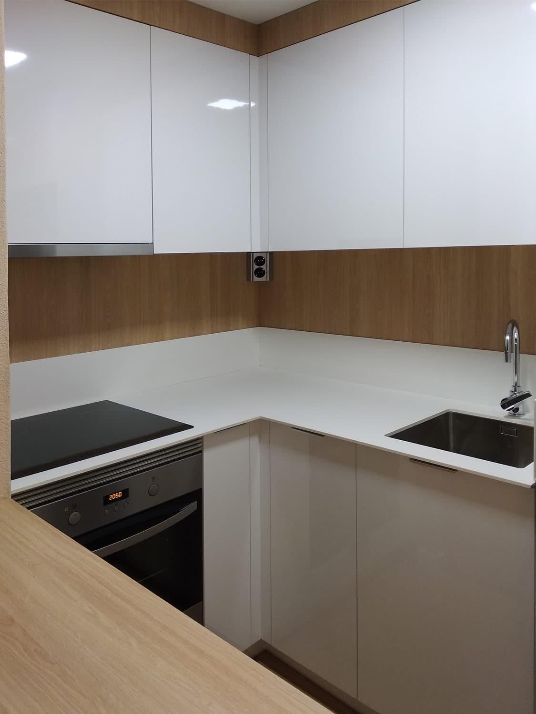 Cocina moderna pequeña en blanco y madera, encimera y copetes altos en blanco a juego.