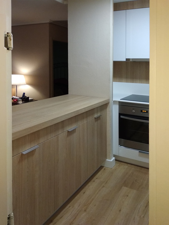Cocina moderna pequeña estilo americana abierta al salón, con frente de muebles en madera.