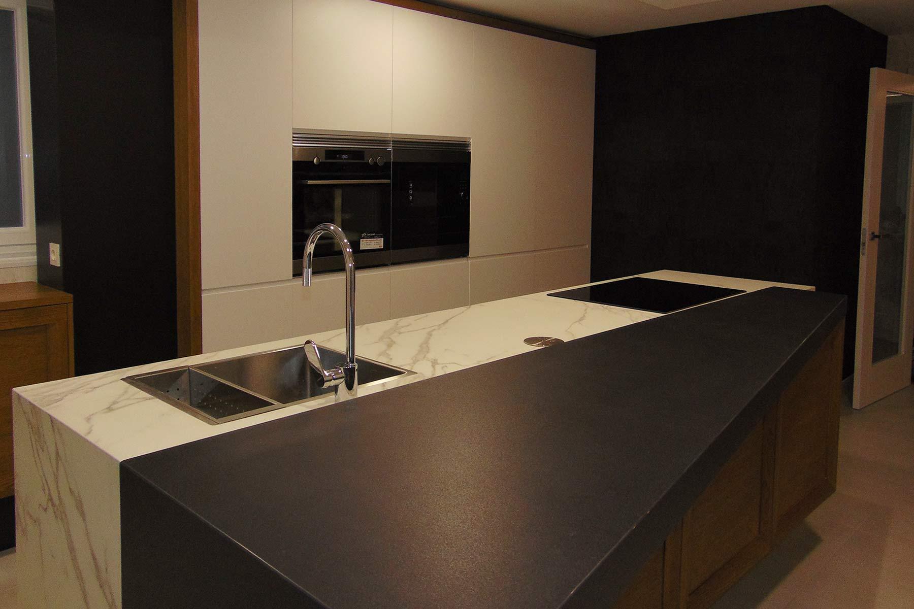 Cocina en isla con encimera en dos acabados y al fondo muebles columna