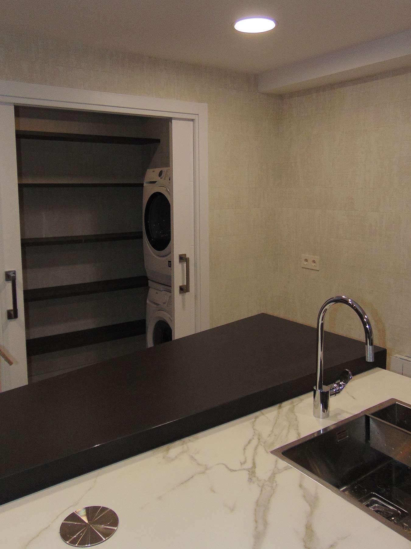 Cocina con zona de lavandería que incluye baldas, lavadora y secadora