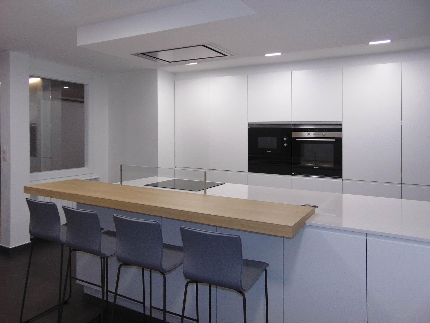 Cocina blanca con distribución en península y frente de muebles columna al fondo.