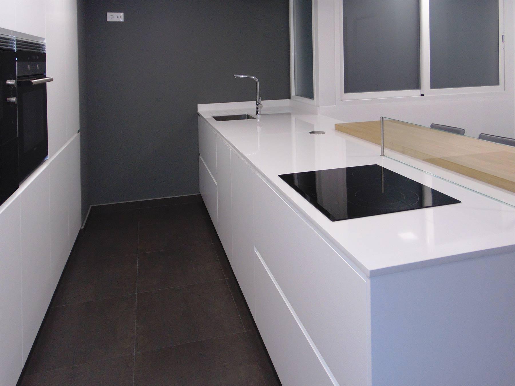 Detalle de la península de cocina. Puertas y encimera en color blanco. Placa de cocción y fregadero integrados.