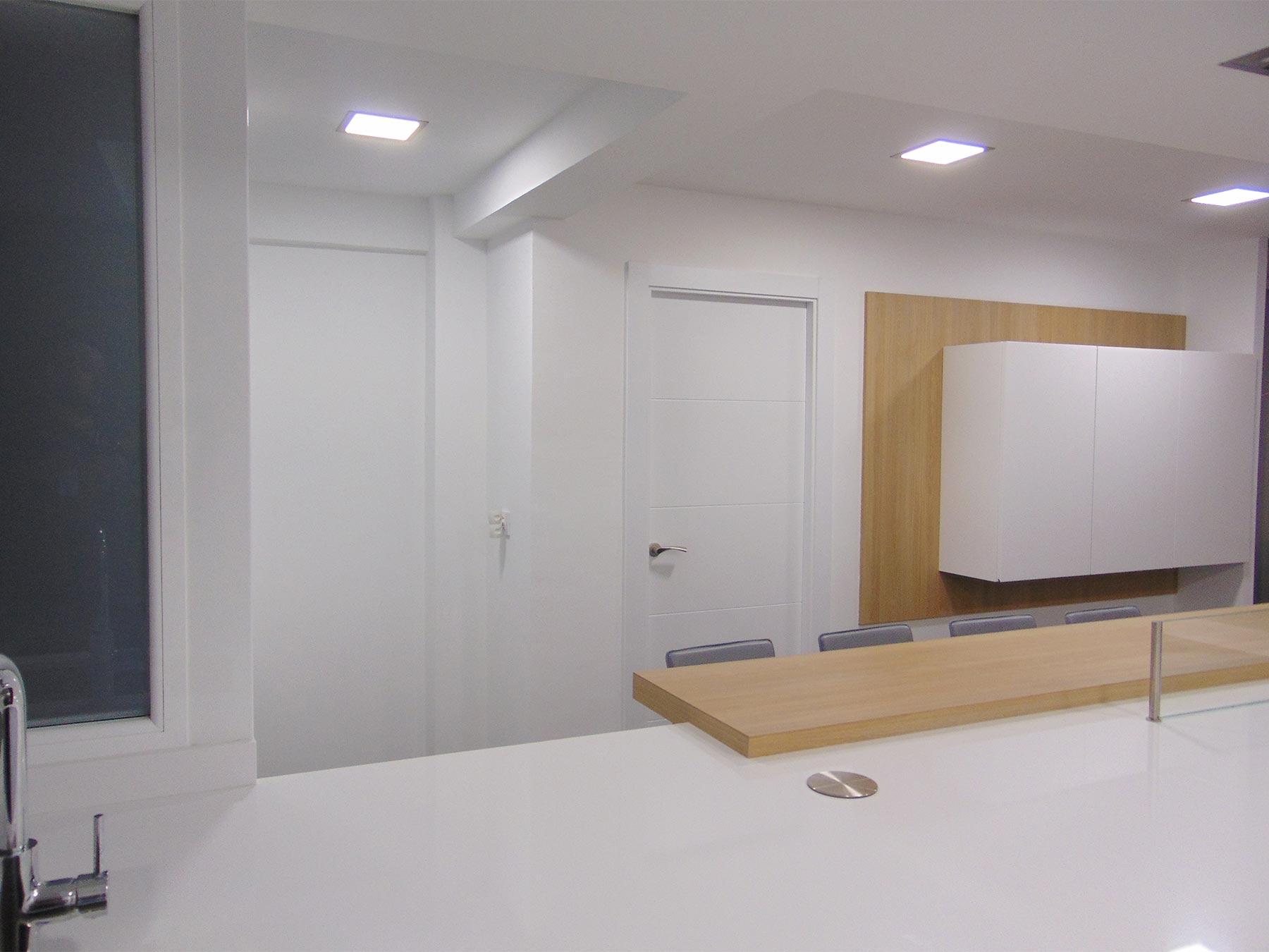 Cocina en blanco brillo con muebles altos suspendidos, con forro de pared en acabado madera.