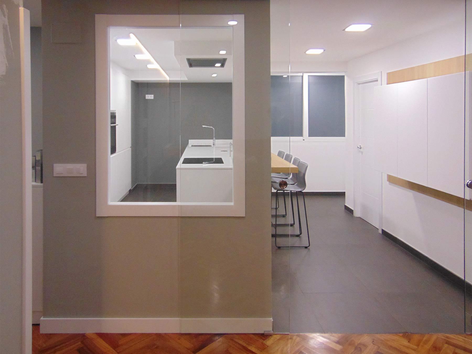 Vista de cocina en color blanco brillo, abierta al salón.