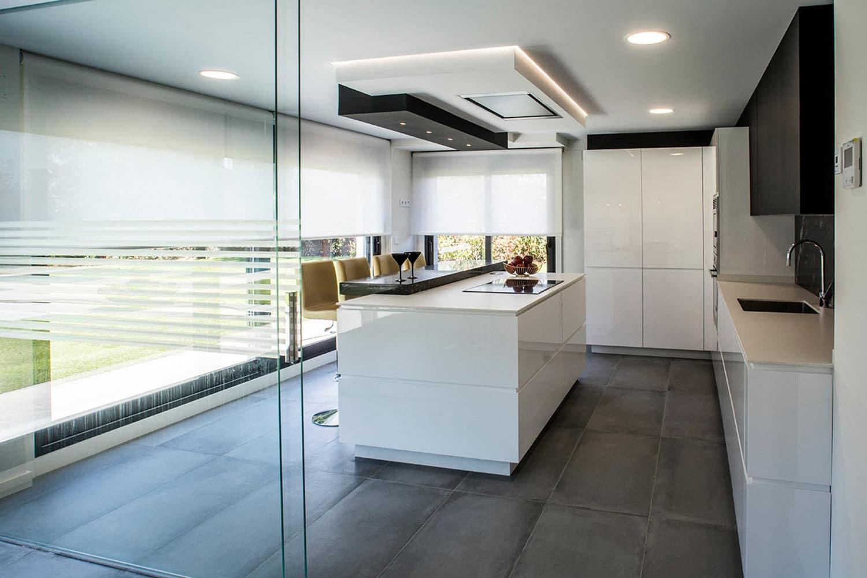 Cocina en isla blanca con barra de desayuno y amplios ventanales