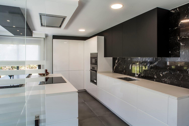 Cocina blanca y negra con frente e isla y muebles en rincón
