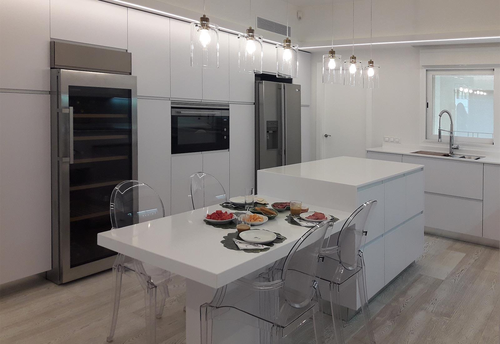 """Cocina en blanco brillo con isla central y mesado, mueble columna con horno integrado, frigorífico """"side by side"""" y vinoteca"""