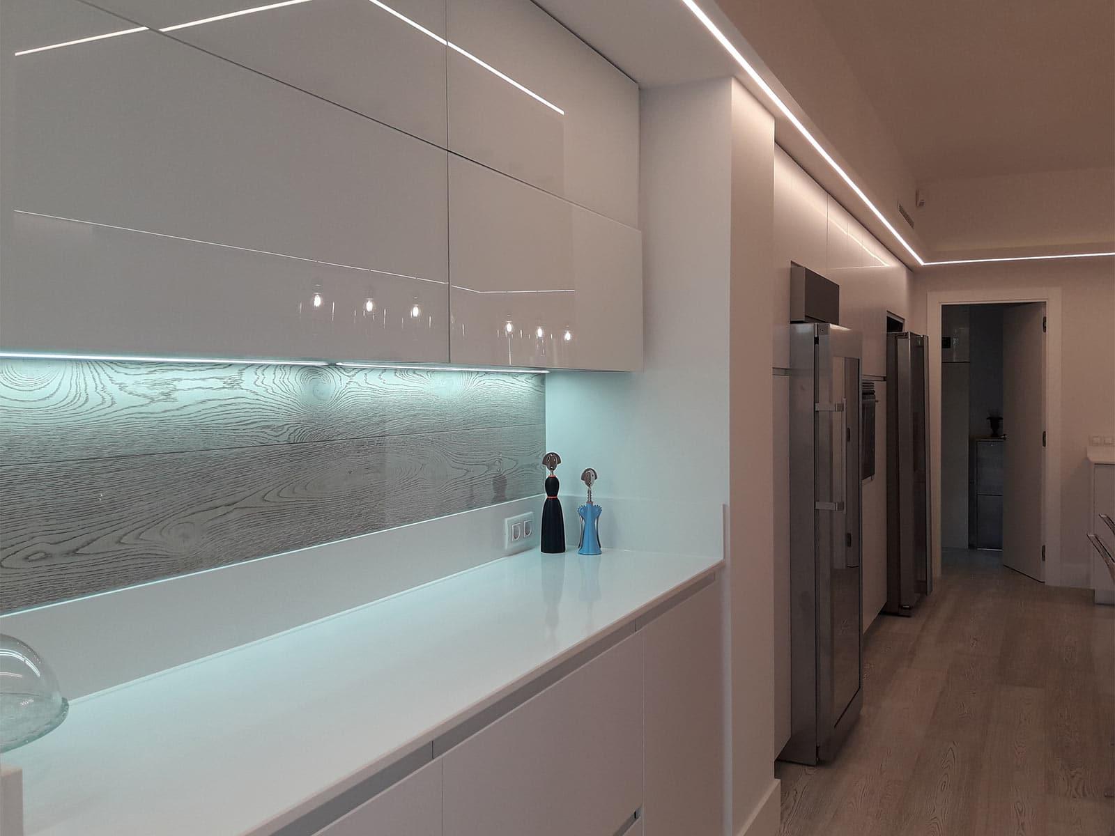 Frente de muebles blanco brillo en cocina lineal doble con isla