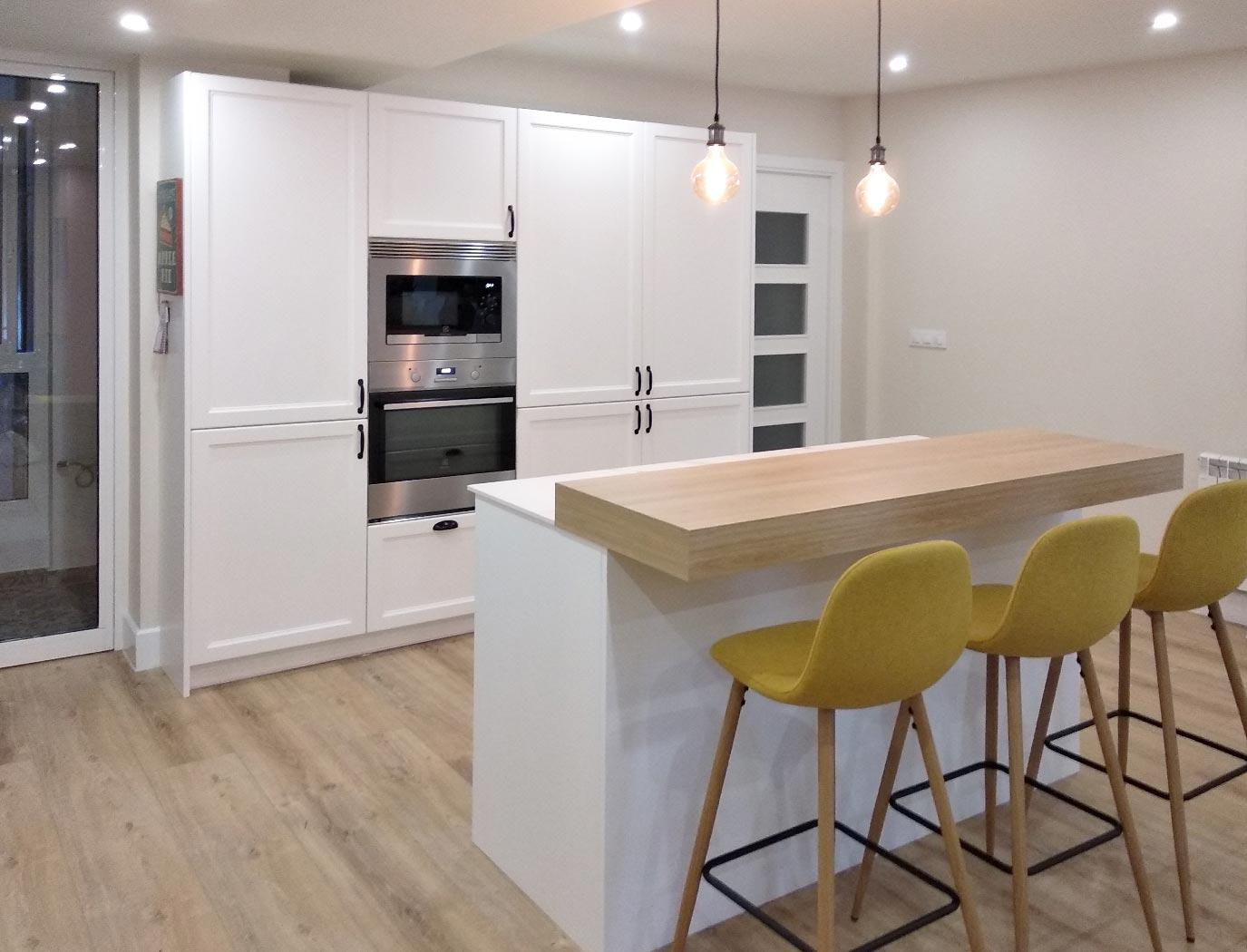 Cocina en isla con frente de muebles columna con frigorífico y congelador integrados.
