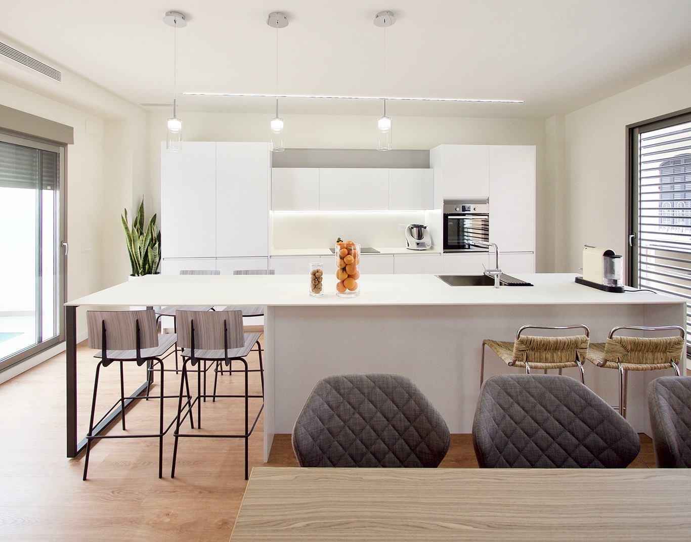 Vista frontal de una cocina con isla blanca y abierta salon comedor