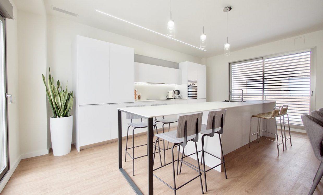 Vista perspectiva de isla de cocina blanca, con estructura de acero
