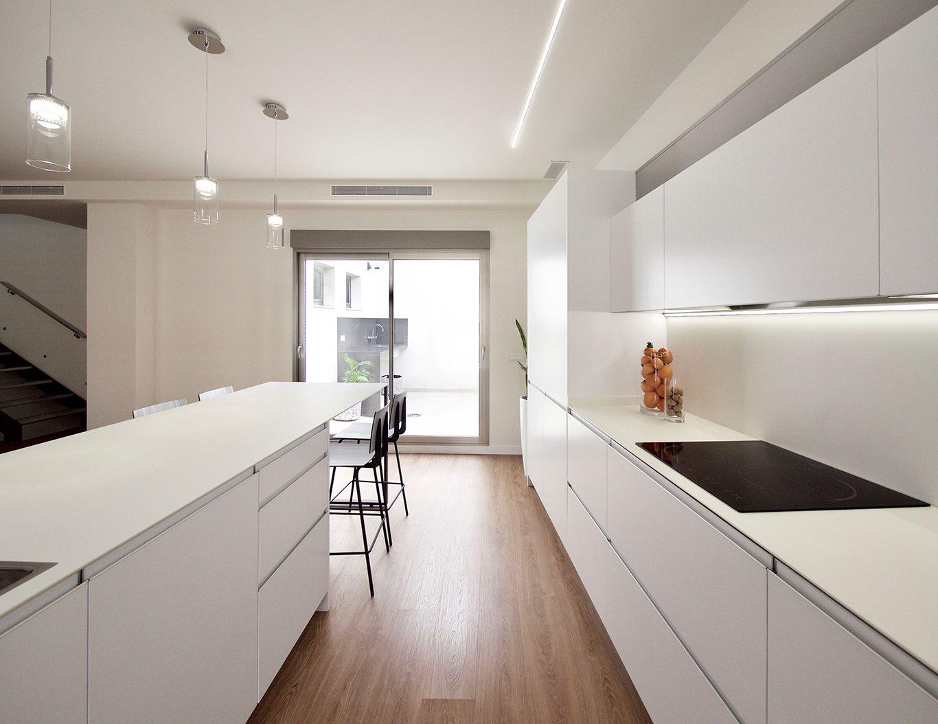 Pasillo de cocina entre isla y frente de muebles bajos y columnas. Color blanco