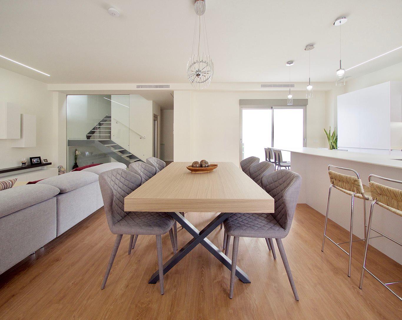 Detalle de mesa de comedor en madera, con salón a la izquierda e isla de cocina a la derecha