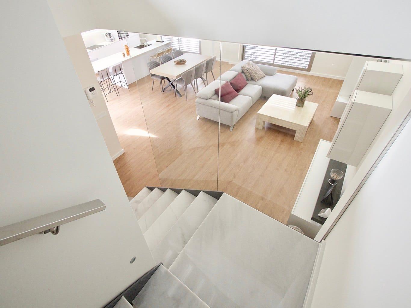 Vista desde las escaleras de salón comedor con suelo en madera y cocina blanca con isla al fondo