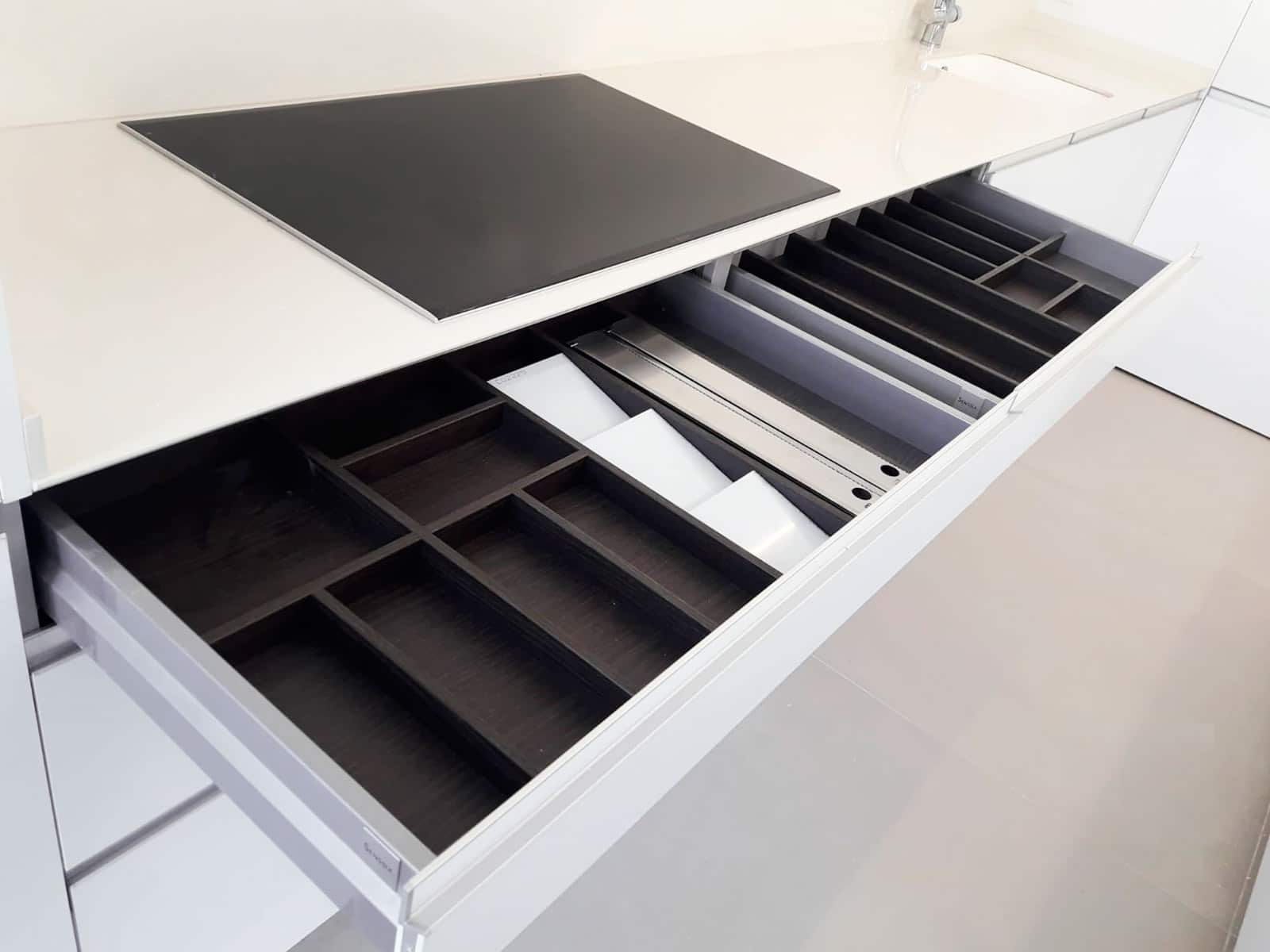 Vista de cuberteros de madera en cajón de mueble bajo placa de cocina