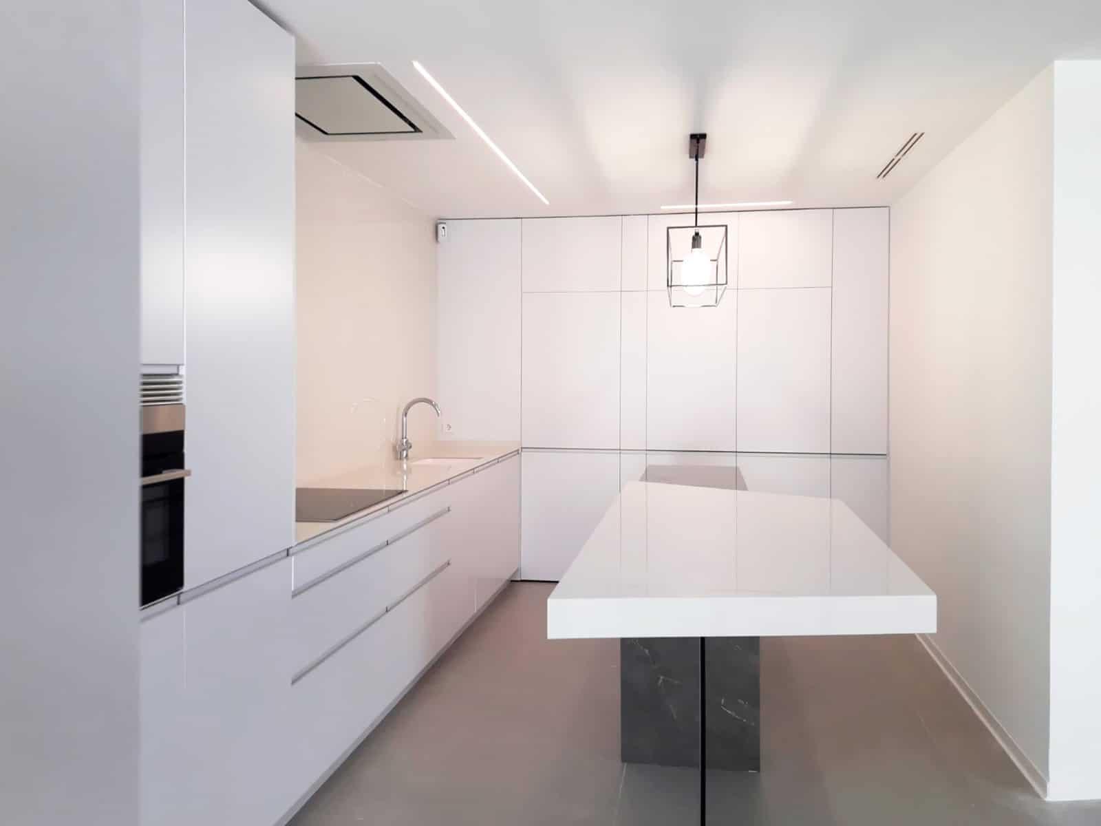 Vista general de cocina en color blanco mate distribuida en ele y con isla central