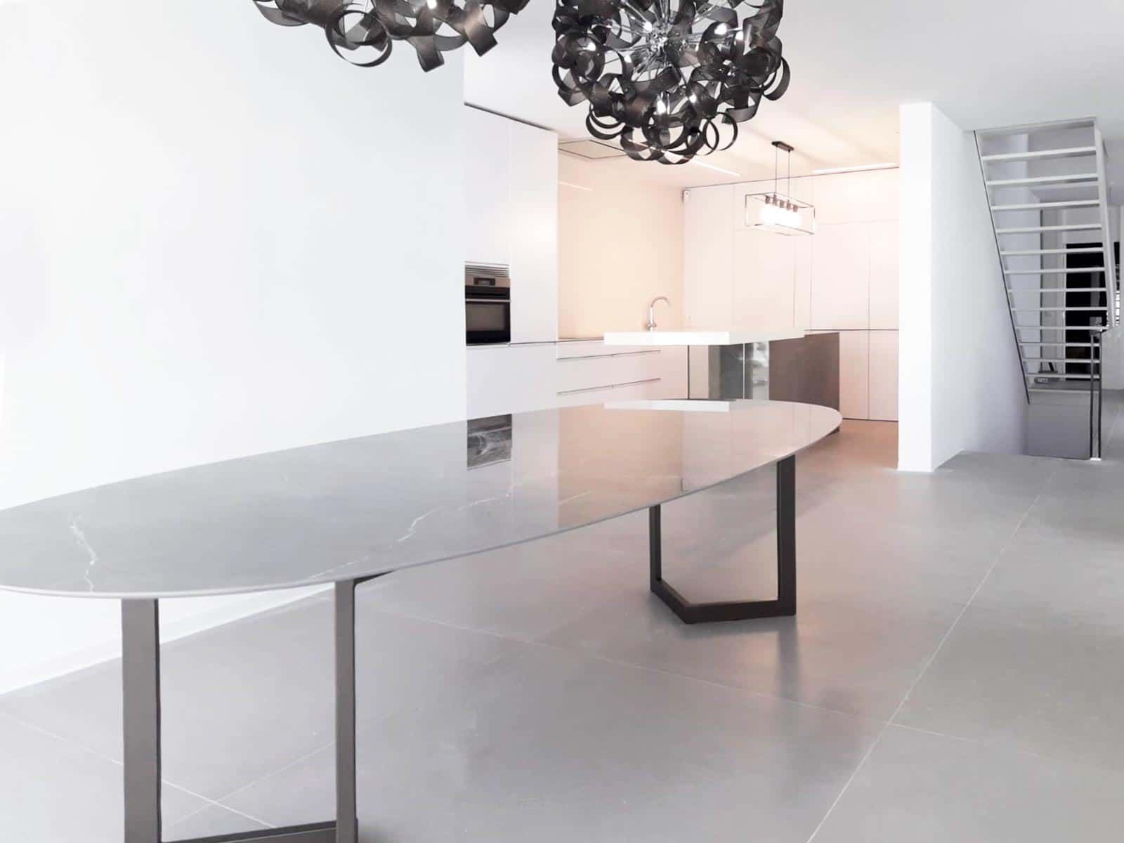 Detalle de mesa de comerdor en forma de óvalo y cocina en color blanco mate al fondo