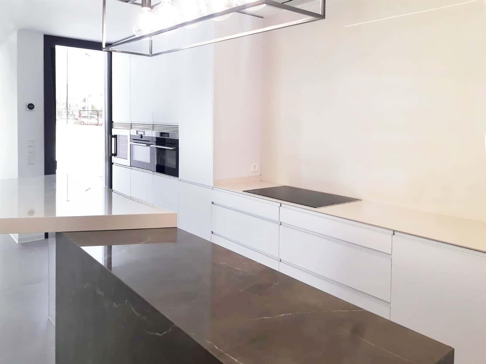 Vista de frente de muebles bajos y columnas de cocina moderna en color blanco mate y tirador embutido