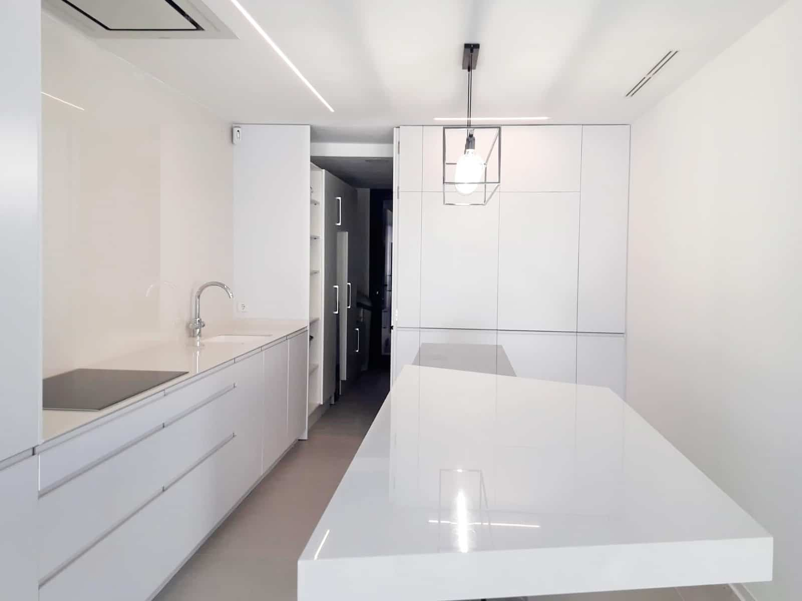 Vista de cocina con frente de muebles columna que dan acceso a zona de lavandería