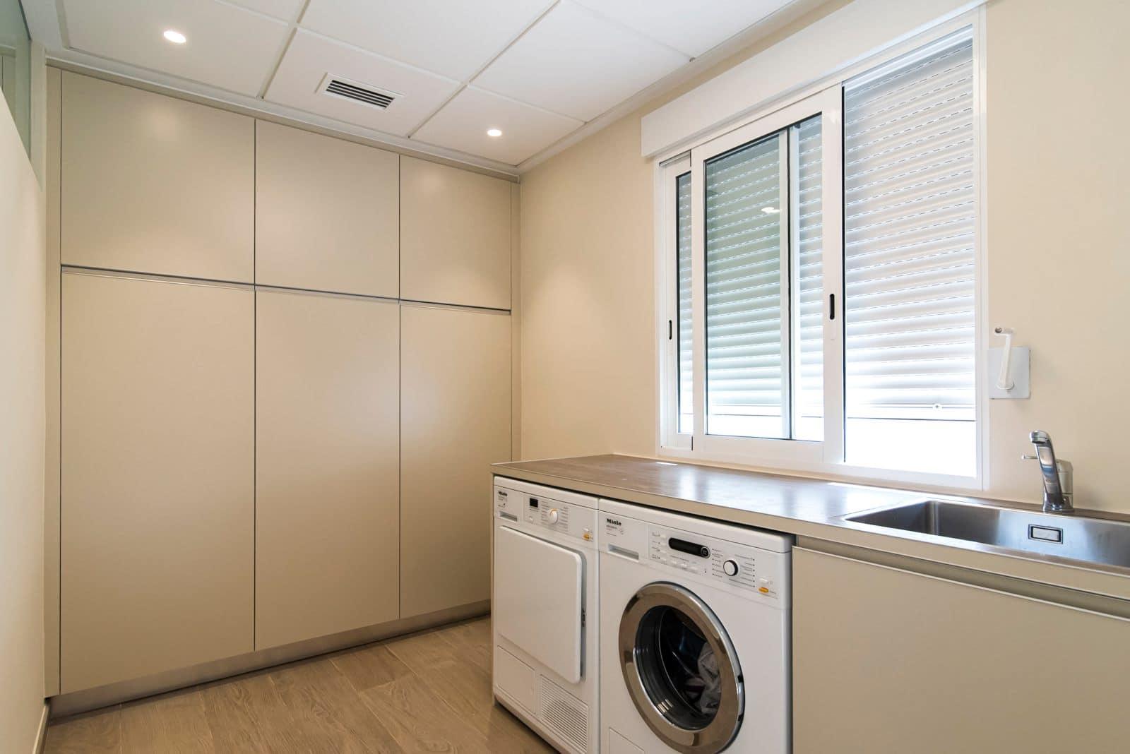 lavandería con secadora, fregadero y armarios