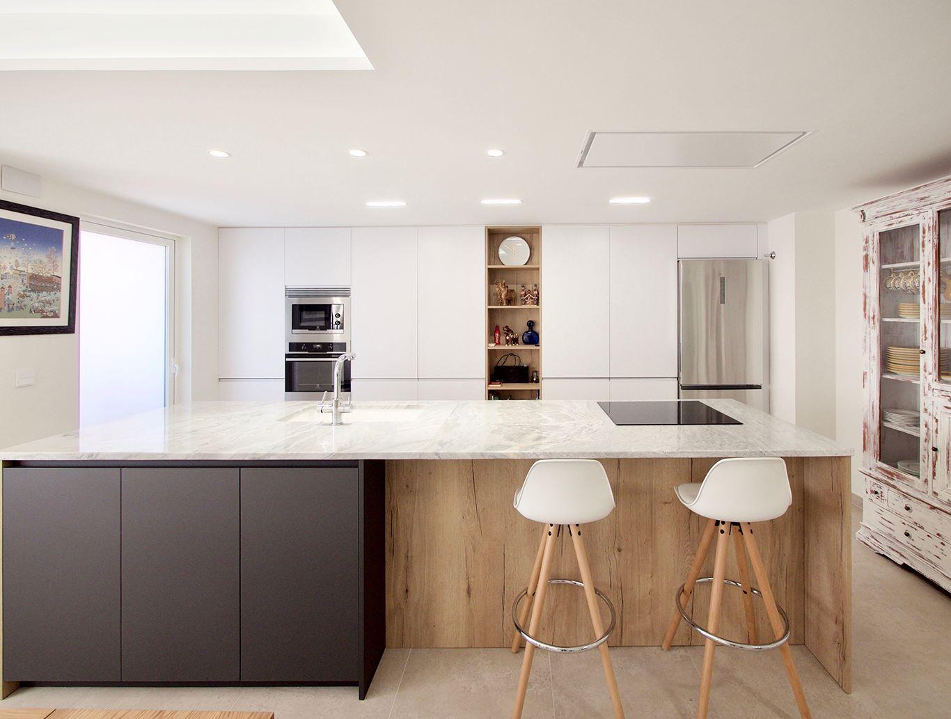 Cocina con mucho espacio de almacenamiento. Distribuida en isla con detalles en madera y gris antracita, con frente de muebles columna en blancos al fondo
