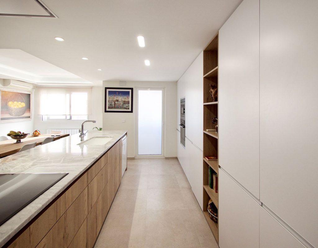 Vista de isla de cocina en madera y frente de muebles columna en blanco, que aportan gran capacidad de almacenamiento