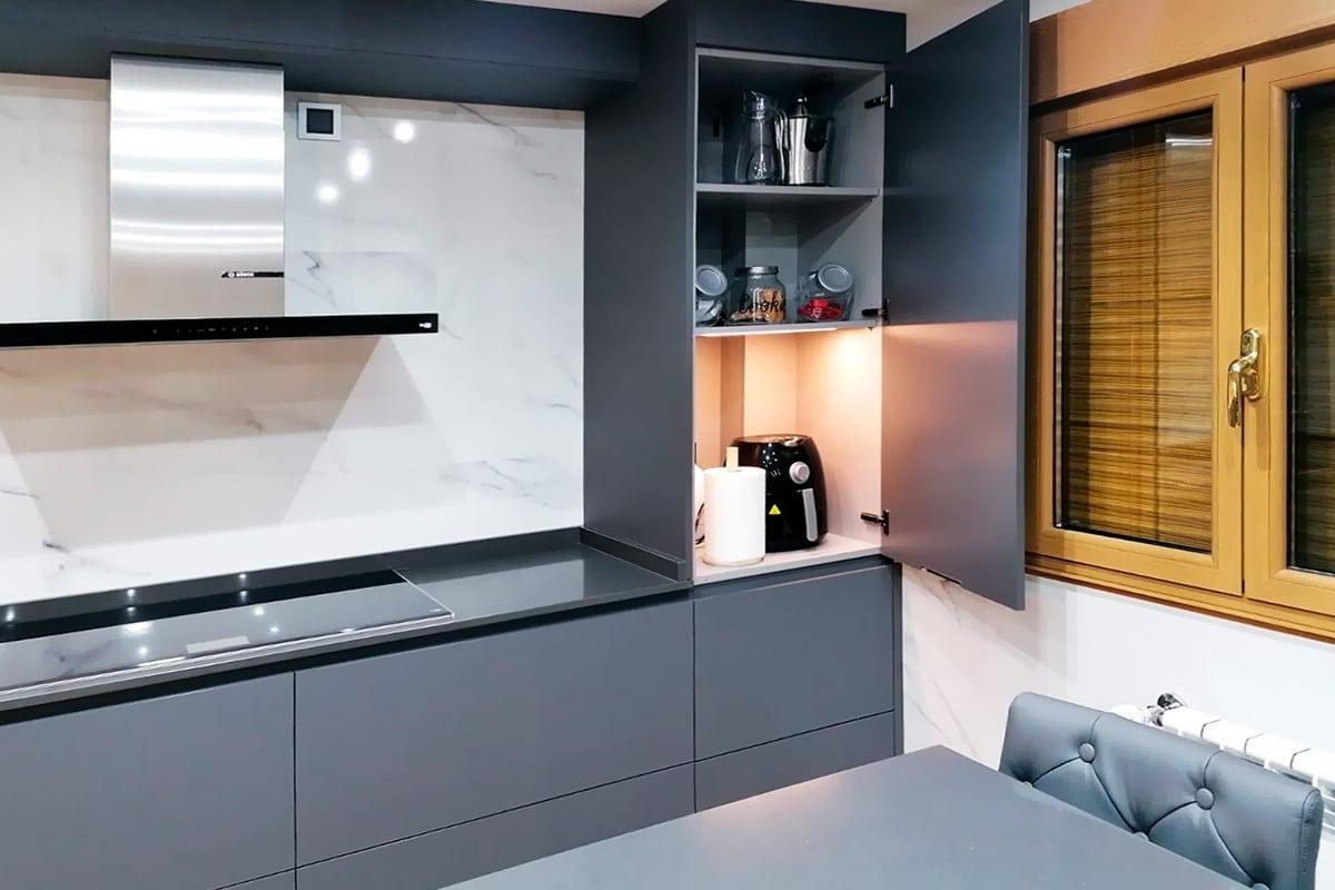Zona de placa y campana de la cocina con un mueble alto sobreencimera abierto