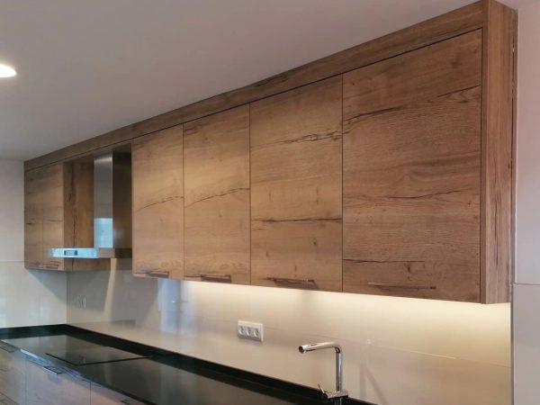 Detalle de muebles altos con LED inferios en una cocina clasica en madera con tirador