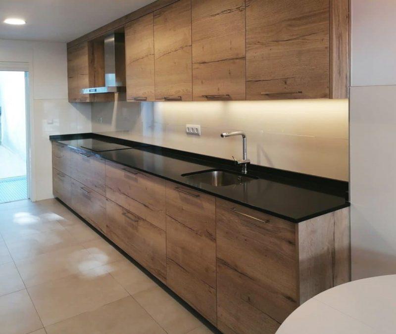 Frente de mueblas bajos y altos en cocina clasica en madera con tirador