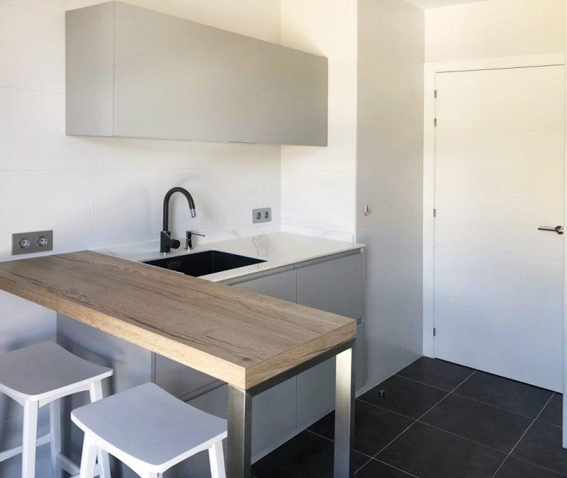Fregadero de cocina blanca con encimera en gris. Mueble alto y barra de desayuno