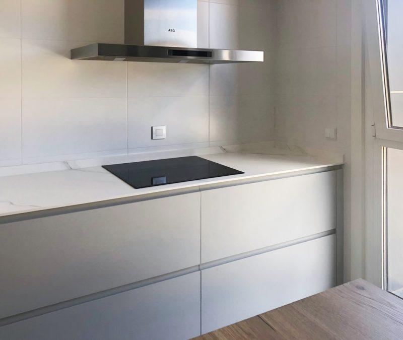 Zona de placa de cocina en color gris con campana a pared