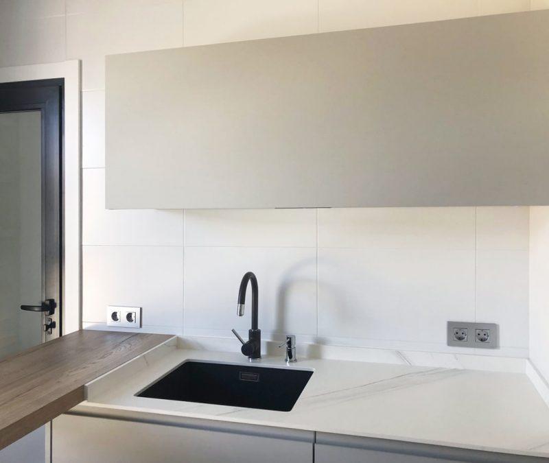 Mueble alto abatible de cocina en color gris sobre fregadero negro