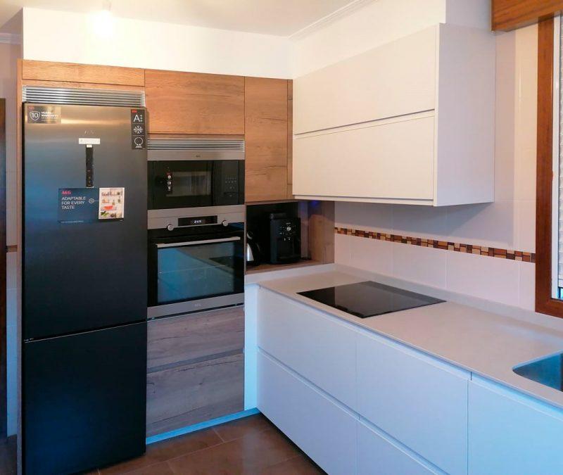 Frentes de cocina distribuidos en ele, con muebles bajos y altos en color blanco y muebles columna en madera