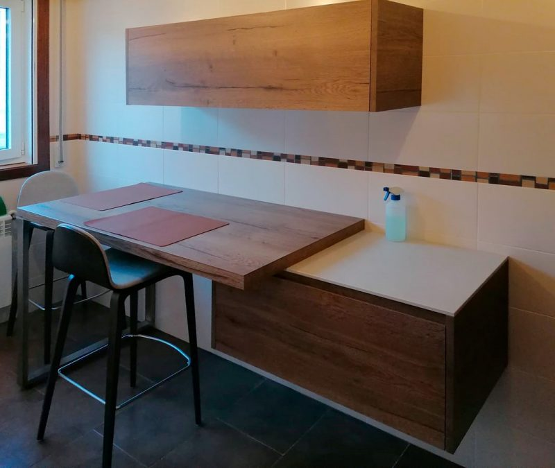Cocina con zona de desayuno en color madera con muebles bajos y altos