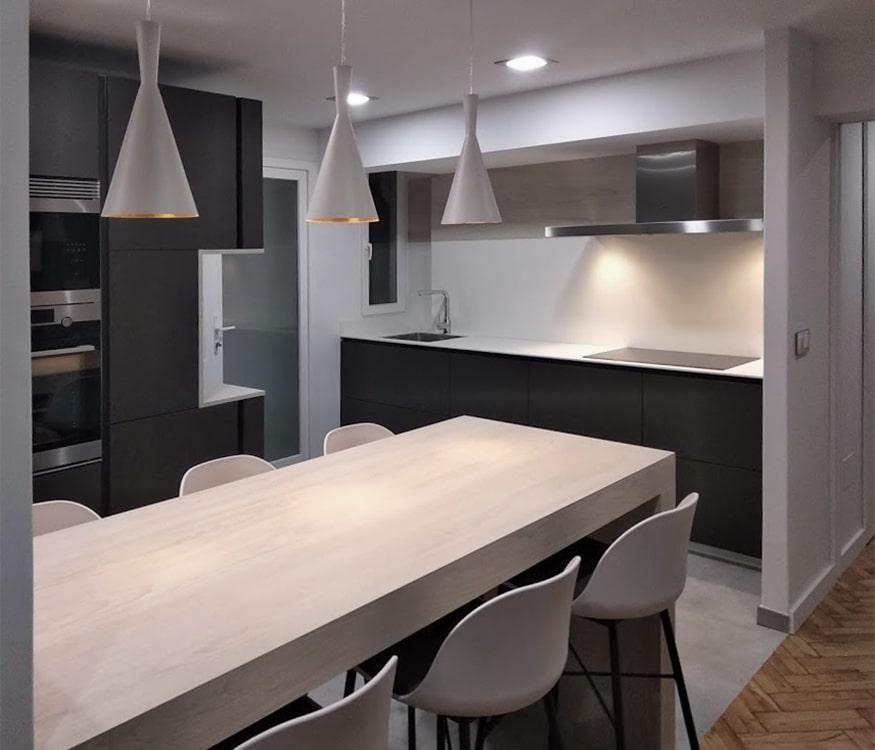 Vista de barra de cocina con frente de muebles de cocina en color gris y encimera blanca
