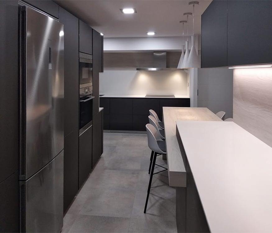 Frente de muebles en gris a la izquierda y muebles bajos y altos, en color gris y encimera blanca