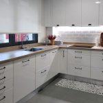 Cocina en color blanco brillo con distribución en U. Tiradores de asa en muebles bajos y de cazoleta en muebles altos. Encimera en acabado madera.
